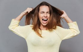 frustrated woman screaming at her hair